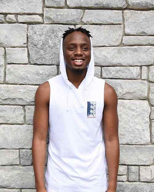 Mark Christie stands in front of a stone wall and smiles. He is wearing a white sleeveless hooded sweatshirt.
