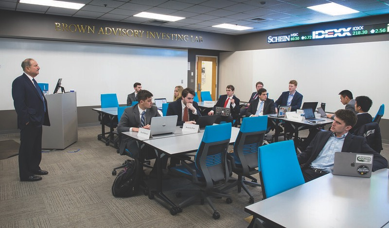 Eleven formally-dressed students work in the Brown Advisory Investing Lab under the supervision of an older advisor.