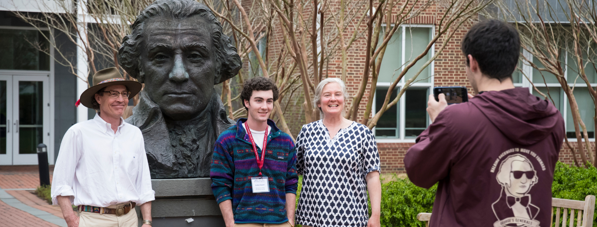 parents and child posing with the george washington statue at admitted students day