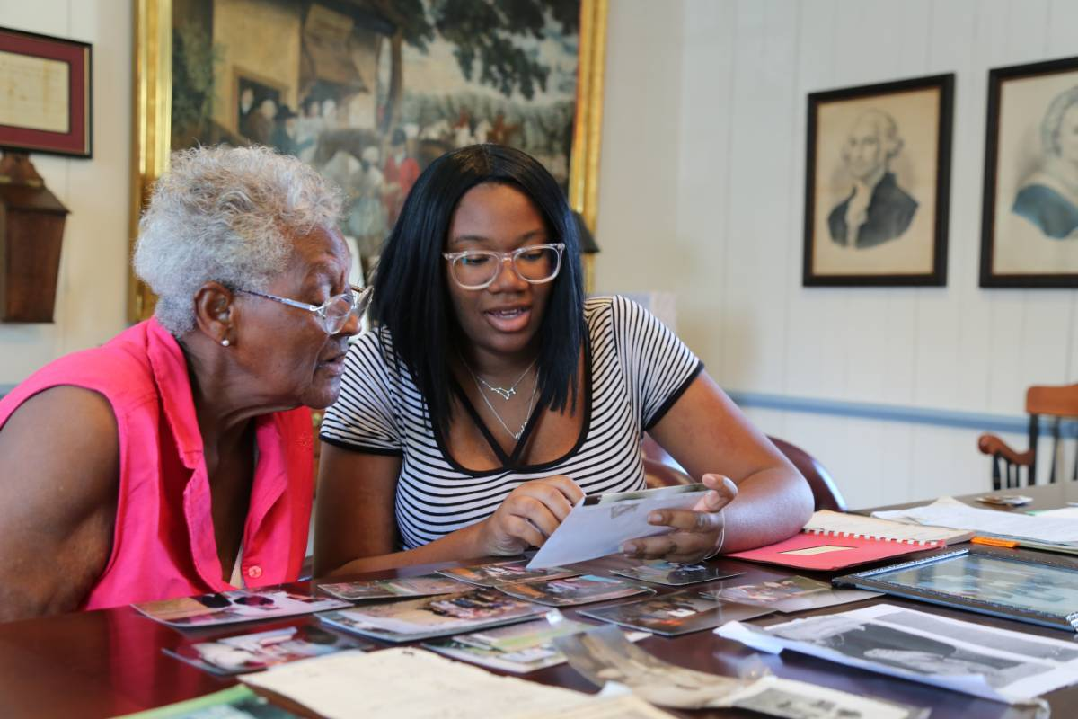 Paris Young, a political science major, works with Georgetown, Maryland, resident Irene Moore to document newspaper clippings and photos about a segregated one-room schoolhouse in Worton which Moore attended.